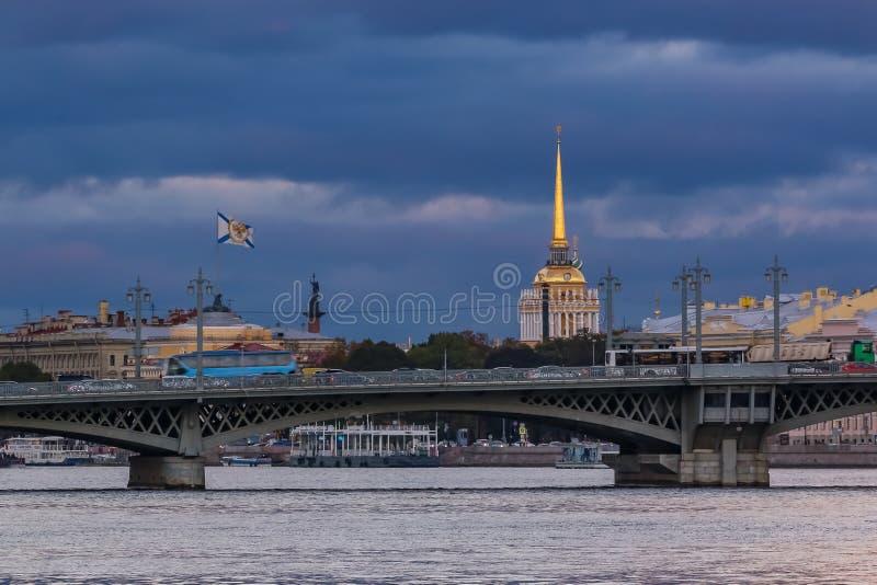 Ηλιοβασίλεμα σε Άγιο Πετρούπολη πέρα από τον ποταμό Neva με την άποψη της γέφυρας Blagoveshchenskiy και του κώνου ναυαρχείου ή Ad στοκ εικόνες με δικαίωμα ελεύθερης χρήσης