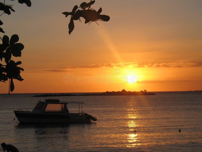 Ηλιοβασίλεμα στην παραλία με μια βάρκα, ένα νησί και leves στοκ φωτογραφία με δικαίωμα ελεύθερης χρήσης