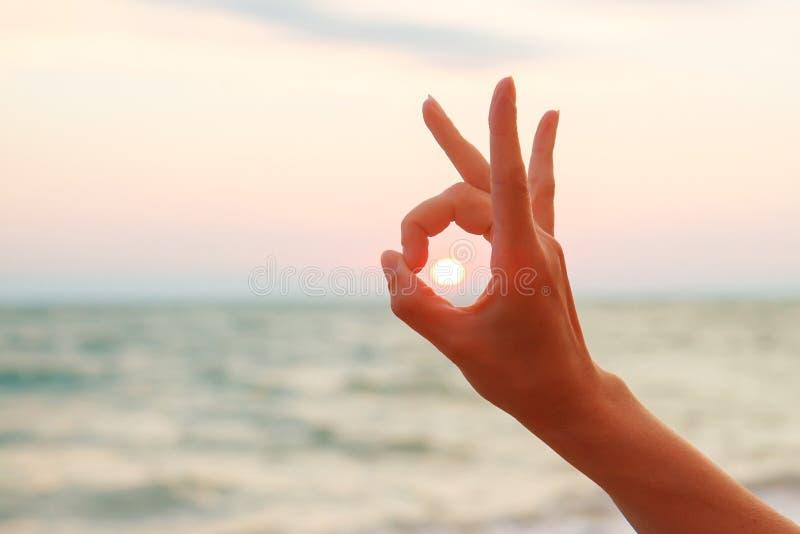 Ηλιοβασίλεμα που συλλαμβάνεται με το χέρι κάτω από το ΕΝΤΑΞΕΙ σημάδι στοκ φωτογραφία