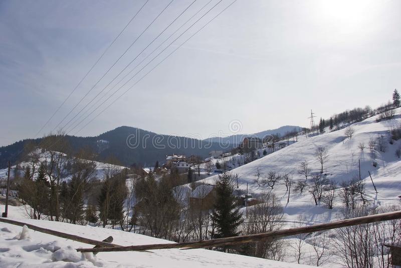 Ηλιόλουστη ημέρα, άποψη από το παράθυρο σε ένα χιονώδες χειμερινό τοπίο Ορεινό χωριό, σπίτια και φράκτες στοκ φωτογραφίες με δικαίωμα ελεύθερης χρήσης