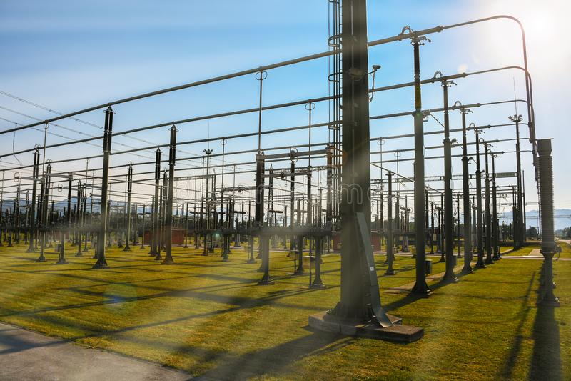Ηλιόλουστη ημέρα σε έναν πράσινο σταθμό εγκαταστάσεων παραγωγής ενέργειας ηλεκτρικής ενέργειας χλόης στοκ εικόνες