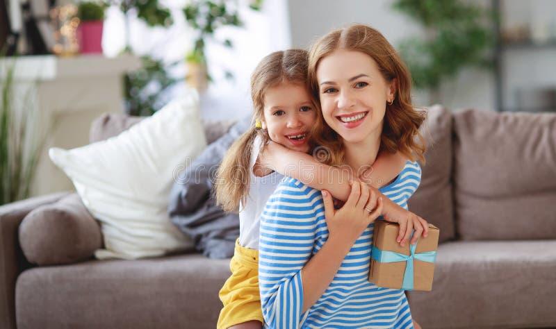 Ημέρα της ευτυχούς μητέρας! η κόρη παιδιών δίνει στη μητέρα μια ανθοδέσμη των λουλουδιών στην τουλίπα και το δώρο στοκ εικόνα