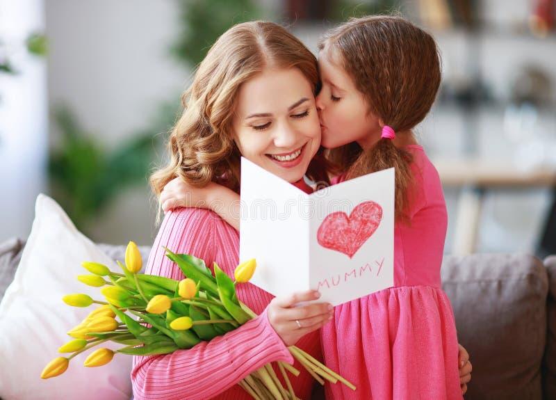 Ημέρα της ευτυχούς μητέρας! η κόρη παιδιών δίνει στη μητέρα μια ανθοδέσμη των λουλουδιών στις τουλίπες και την κάρτα στοκ εικόνες