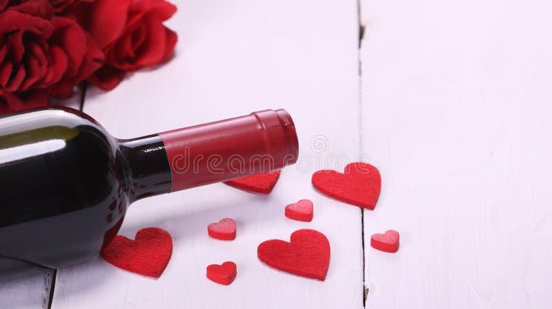 Ημέρα του ευτυχούς βαλεντίνου με το κόκκινο κρασί, τα κόκκινα τριαντάφυλλα, το άσπρες υπόβαθρο και τις καρδιές στοκ εικόνα