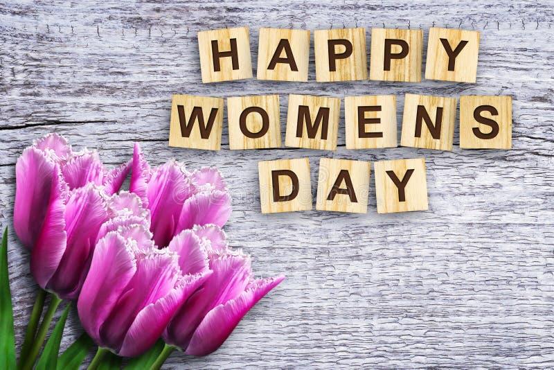 Ημέρα των ευτυχών γυναικών, η επιγραφή αποτελείται από το αλφάβητο στους ξύλινους κύβους όμορφες τουλίπες Ξύλινη ανασκόπηση στοκ φωτογραφία με δικαίωμα ελεύθερης χρήσης