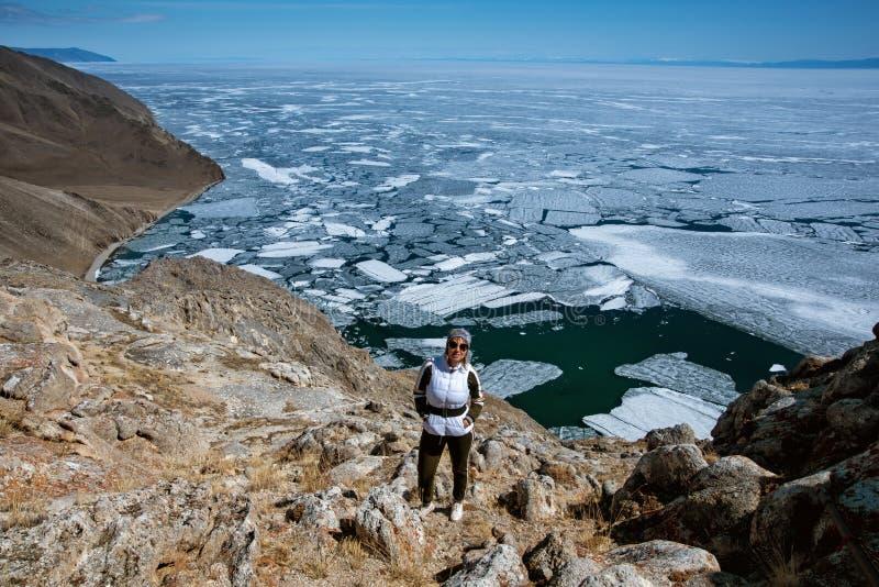 Η άποψη επάνω από τη μεγάλη όμορφη λίμνη Baikal με τους επιπλέοντες πάγους πάγου που επιπλέουν στο νερό με το κορίτσι φορά το άσπ στοκ εικόνες με δικαίωμα ελεύθερης χρήσης