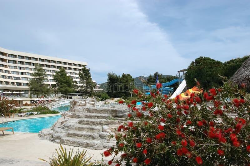Η άποψη του εδάφους και της πισίνας με το νερό γλιστρά μέσα το ελληνικό ξενοδοχείο στοκ εικόνα με δικαίωμα ελεύθερης χρήσης