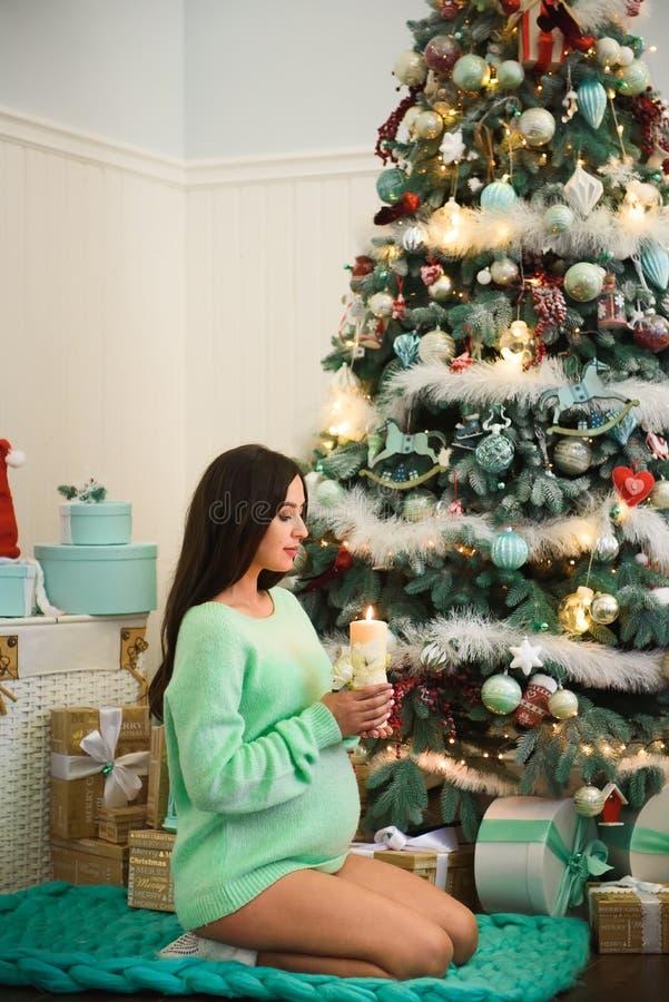 Η έγκυος γυναίκα κάθεται κοντά στο χριστουγεννιάτικο δέντρο με ένα κερί στα χέρια της στοκ φωτογραφία με δικαίωμα ελεύθερης χρήσης