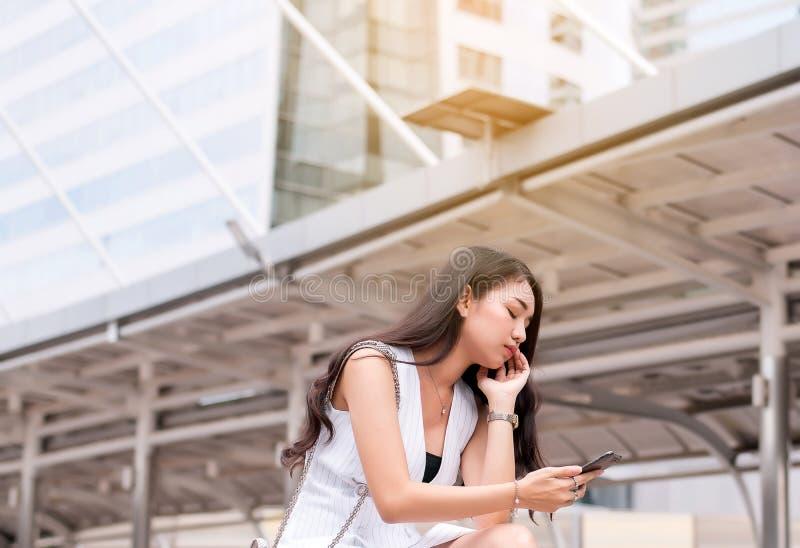 Η έννοια προβλήματος ανεργίας, ασιατική όμορφη γυναίκα τόνισε και κατάθλιψη από την εργασία καθμένος υπαίθριος στοκ εικόνα με δικαίωμα ελεύθερης χρήσης
