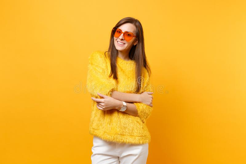 Η αρκετά χαμογελώντας νέα γυναίκα στο πουλόβερ γουνών, άσπρα εσώρουχα, πορτοκαλιά eyeglasses καρδιών που κρατά τα χέρια δίπλωσε α στοκ φωτογραφίες με δικαίωμα ελεύθερης χρήσης