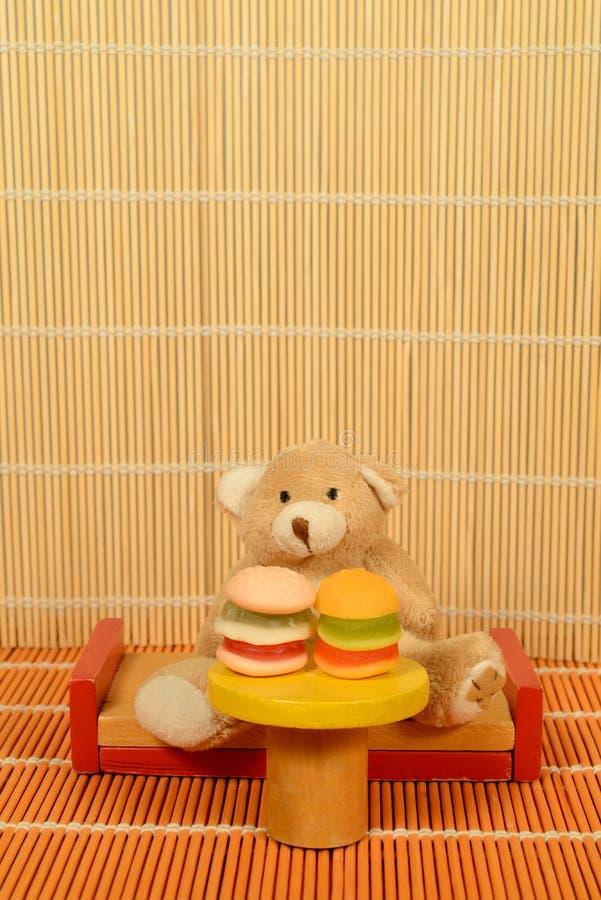 Η βουλιμία Teddy γρήγορου φαγητού αντέχει στα επιτραπέζια χάμπουργκερ στοκ φωτογραφία με δικαίωμα ελεύθερης χρήσης