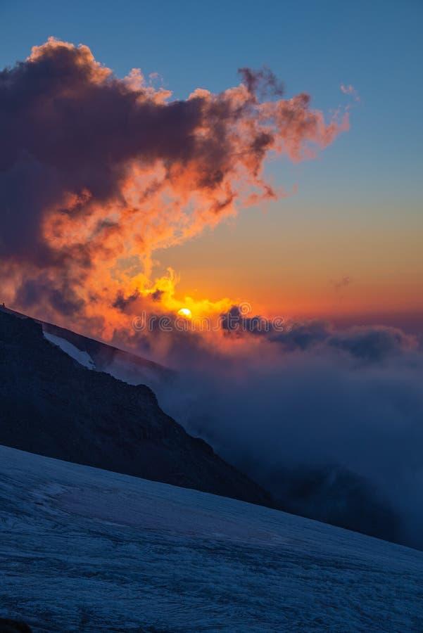 Η βόρεια πλευρά Elbrus Ηλιοβασίλεμα υψηλό στα βουνά με τον πορτοκαλή ήλιο και τα παχιά ρόδινος-ιώδη σύννεφα στοκ εικόνες με δικαίωμα ελεύθερης χρήσης