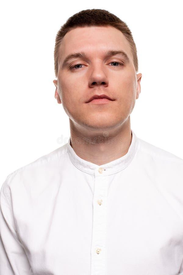 Η γοητεία του όμορφου νεαρού άνδρα σε ένα άσπρο πουκάμισο κάνει τα πρόσωπα, στεμένος που απομονώνεται σε ένα άσπρο υπόβαθρο στοκ εικόνες