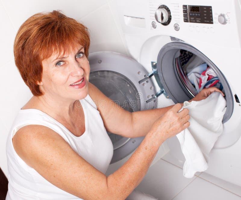 Η γυναίκα βάζει τα ενδύματα στο πλυντήριο στοκ εικόνα με δικαίωμα ελεύθερης χρήσης