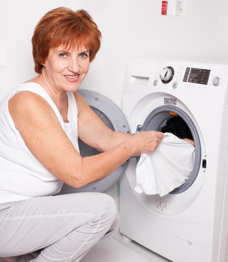 Η γυναίκα βάζει τα ενδύματα στο πλυντήριο στοκ εικόνες