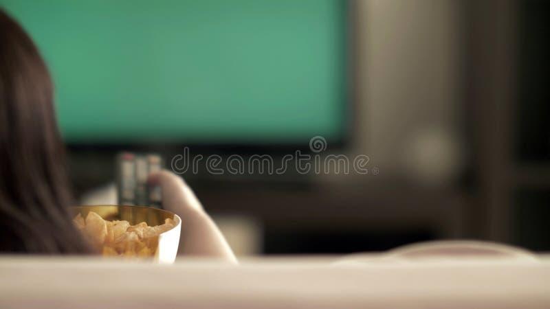 Η γυναίκα ξοδεύει ελεύθερου χρόνου TV οθόνης προσοχής την πράσινη στον καναπέ στο σπίτι, που τα τσιπ στοκ εικόνες με δικαίωμα ελεύθερης χρήσης