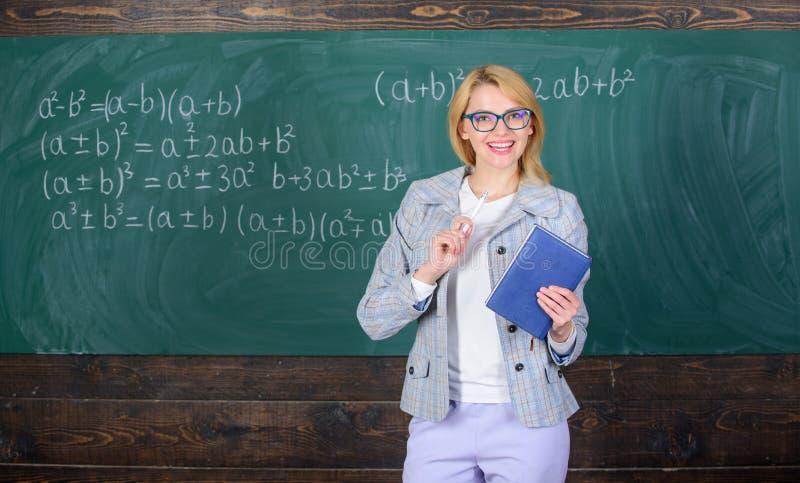 Η γυναίκα δασκάλων εξηγεί κοντά στον πίνακα κιμωλίας Τα ποια κάνουν το μεγάλο δάσκαλο Ο δάσκαλος σχολείου εξηγεί τα πράγματα καλά στοκ εικόνες