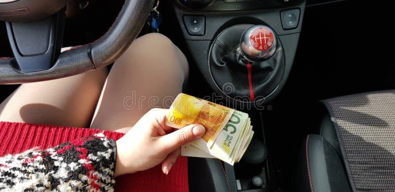 Η γυναίκα στο κόκκινο μίνι φόρεμα στο σπορ αυτοκίνητο κρατά στον ισραηλινό σωρό χρημάτων χεριών της νέων Shekel στοκ εικόνα