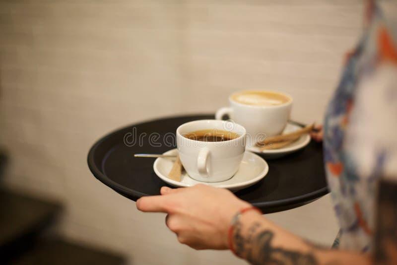 Η γυναίκα φέρνει δύο άσπρα φλυτζάνια του latte και του americano coffe στο δίσκο στοκ φωτογραφία
