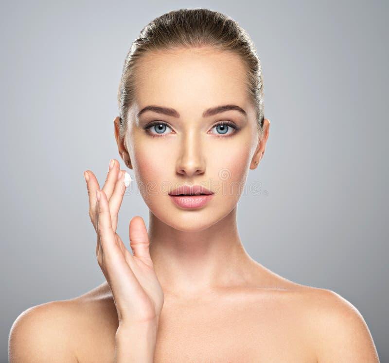 Η γυναίκα παίρνει την κρέμα στο πρόσωπο Έννοια φροντίδας δέρματος στοκ φωτογραφία με δικαίωμα ελεύθερης χρήσης