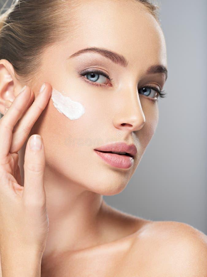 Η γυναίκα παίρνει την κρέμα στο πρόσωπο Έννοια φροντίδας δέρματος στοκ εικόνες