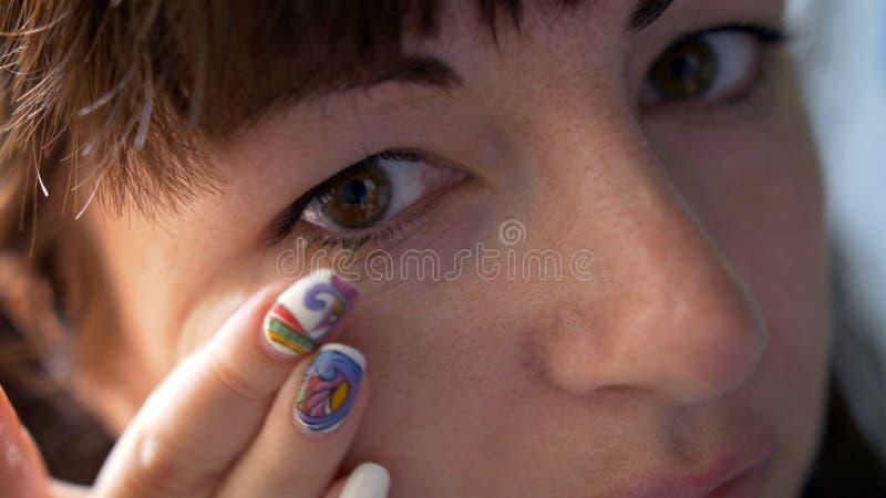 Η γυναίκα που εξετάζει τη κάμερα και φορά την κινηματογράφηση σε πρώτο πλάνο φακών επαφής στοκ εικόνες