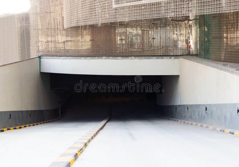 Η είσοδος του υπόγειου χώρου στάθμευσης κοντά στο εργοτάξιο οικοδομής του ουρανοξύστη φιαγμένου από τα φύλλα του ενωμένου στενά π στοκ φωτογραφία