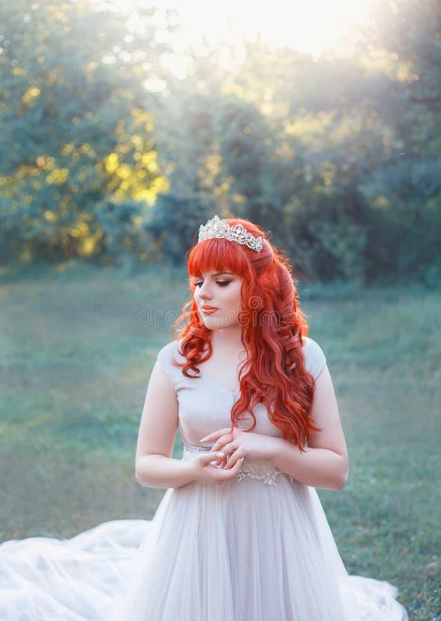 Η εικόνα της δασικής βασίλισσας με τη φωτεινή κόκκινη κατσαρωμένη τρίχα, την τιάρα και το μέτριο χαμόγελο, δίπλωσε ήπια τα χέρια  στοκ φωτογραφίες
