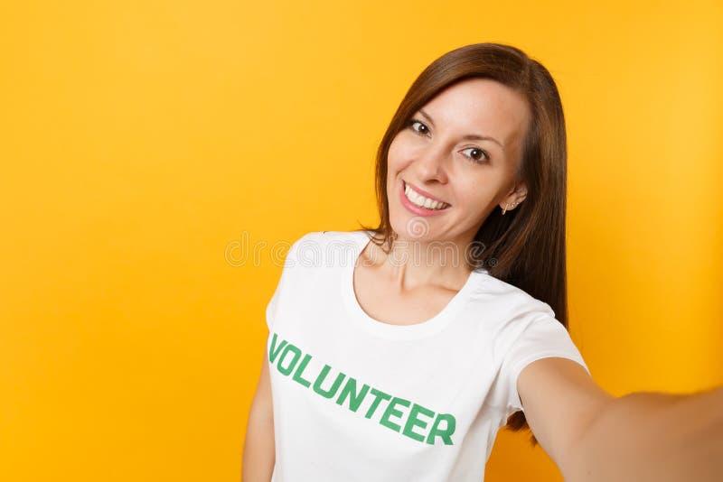 Η εικόνα Selfie του ευτυχούς χαμόγελου ικανοποίησε τη γυναίκα στην άσπρη μπλούζα με τη γραπτή επιγραφή πράσινος εθελοντής τίτλου  στοκ φωτογραφίες