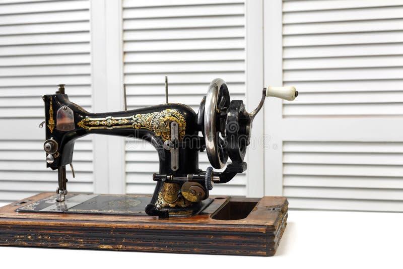 Η εκλεκτής ποιότητας ράβοντας μηχανή στέκεται στον άσπρο πίνακα στοκ εικόνα