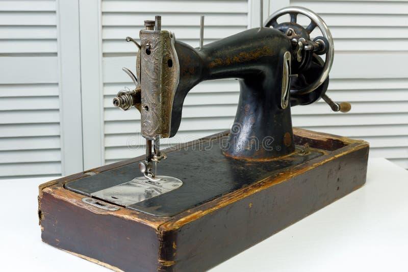 Η εκλεκτής ποιότητας ράβοντας μηχανή στέκεται στον άσπρο πίνακα στοκ φωτογραφίες με δικαίωμα ελεύθερης χρήσης