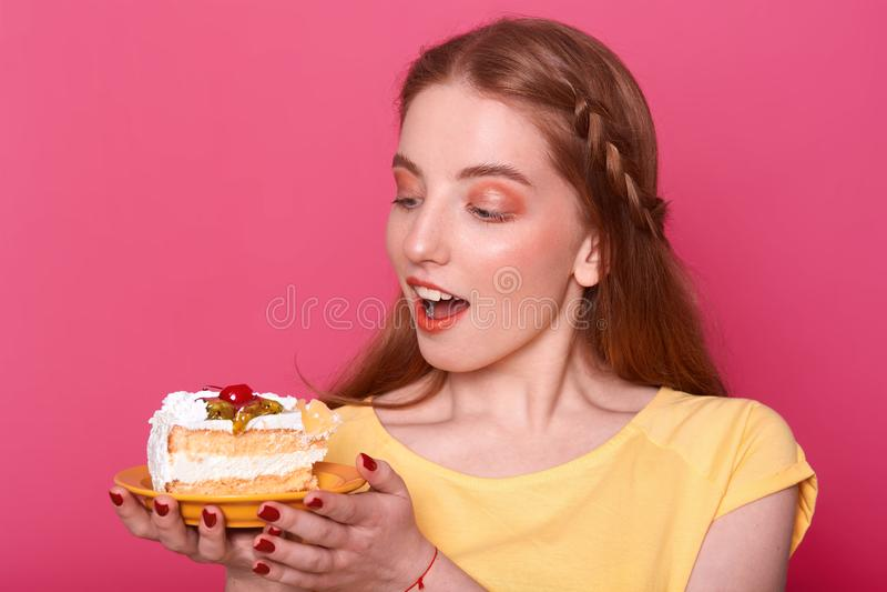 Η ελκυστική νέα γυναίκα με το ανοιγμένο στόμα κρατά το πιάτο με το κομμάτι του εύγευστου κέικ στα χέρια Καφετιά μαλλιαρή κυρία με στοκ εικόνες