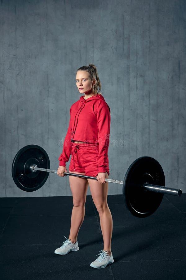 Η ελκυστική νέα φίλαθλη γυναίκα επιλύει στη γυμναστική Η μυϊκή γυναίκα κάθεται οκλαδόν με το barbell στοκ εικόνα