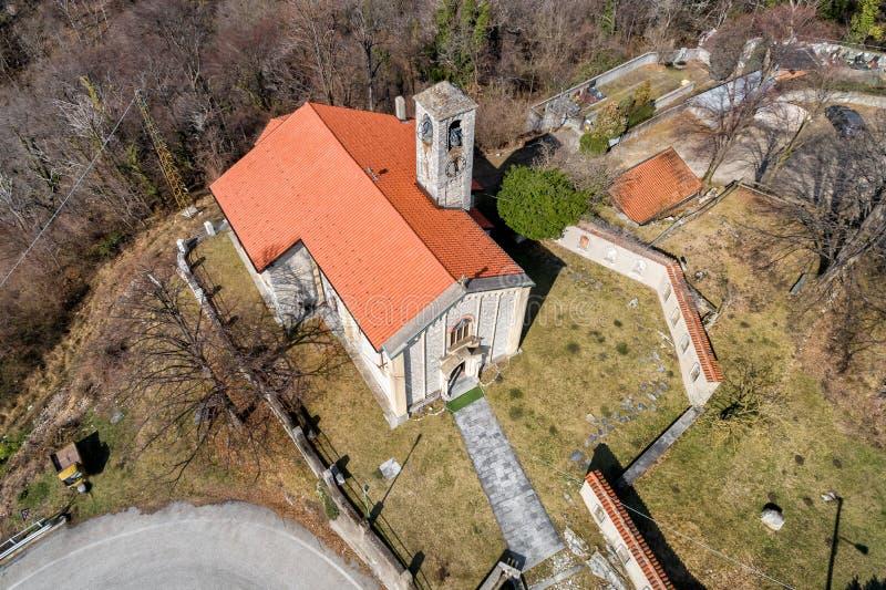 Η εναέρια άποψη Sant Ambrogio Church τοποθέτησε στο χρωματισμένο χωριό Arcumeggia, Βαρέζε, Ιταλία στοκ φωτογραφία