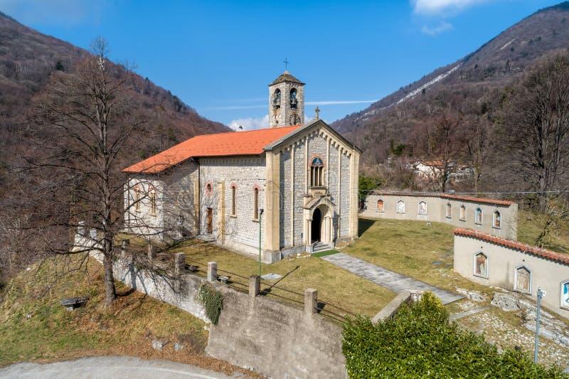 Η εναέρια άποψη Sant Ambrogio Church τοποθέτησε στο χρωματισμένο χωριό Arcumeggia, Βαρέζε, Ιταλία στοκ εικόνες