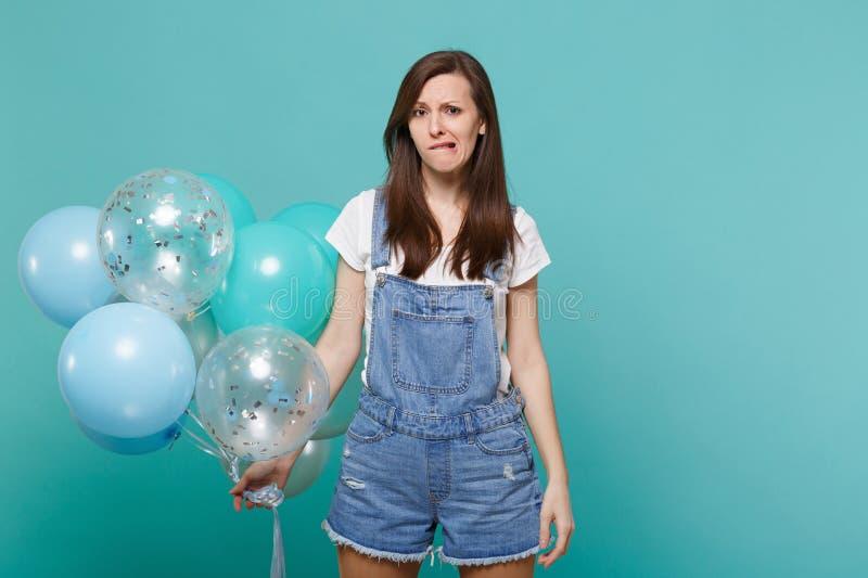 Η ενδιαφερόμενη νέα γυναίκα στο τζιν ντύνει τα χείλια δαγκώματος, εορτασμός και κράτημα των ζωηρόχρωμων μπαλονιών αέρα απομονωμέν στοκ φωτογραφίες