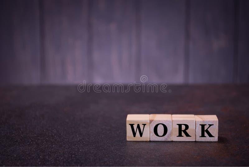 Η εργασία λέξης για τους ξύλινους κύβους, σε ένα σκοτεινό υπόβαθρο, ανάβει τα ξύλινα σημάδια κύβων, σημάδια συμβόλων στοκ εικόνες