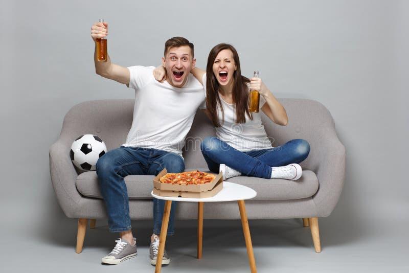 Η ευθυμία οπαδών ποδοσφαίρου ανδρών γυναικών ζευγών κραυγής υποστηρίζει επάνω την αγαπημένη ομάδα με το αγκάλιασμα μπουκαλιών μπύ στοκ φωτογραφίες με δικαίωμα ελεύθερης χρήσης