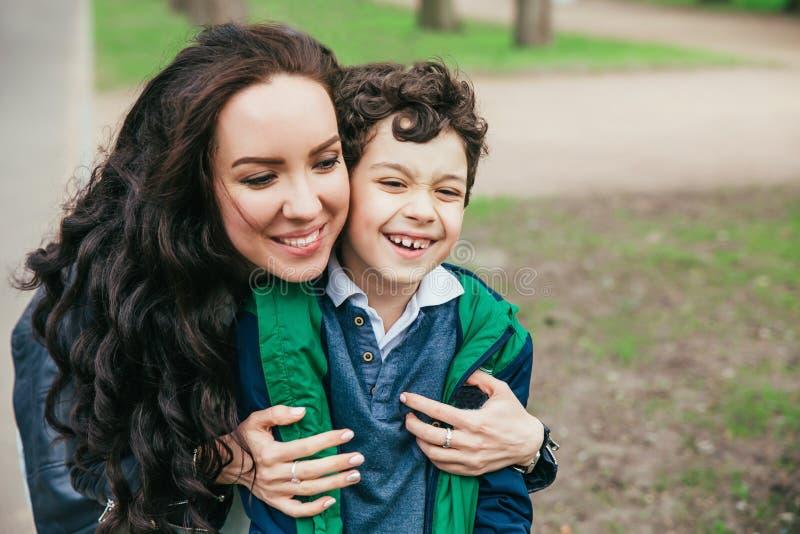 Η ευτυχής οικογένεια σταθμεύει την άνοιξη νέα μητέρα και ο χρόνος εξόδων γιων της υπαίθριοι μια θερινή ημέρα στοκ εικόνες