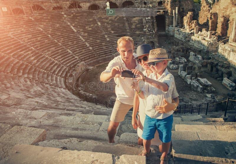 Η ευτυχής οικογένεια παίρνει τη φωτογραφία διακοπών selfie στις παλαιές καταστροφές θεάτρων στην πλευρά, Τουρκία στοκ εικόνες