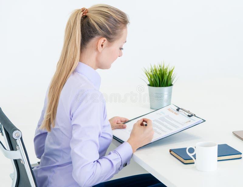 Η επιχειρηματίας που ελέγχει ένα έγγραφο επαναλαμβάνει τη συνέντευξη εργασίας στοκ φωτογραφία με δικαίωμα ελεύθερης χρήσης