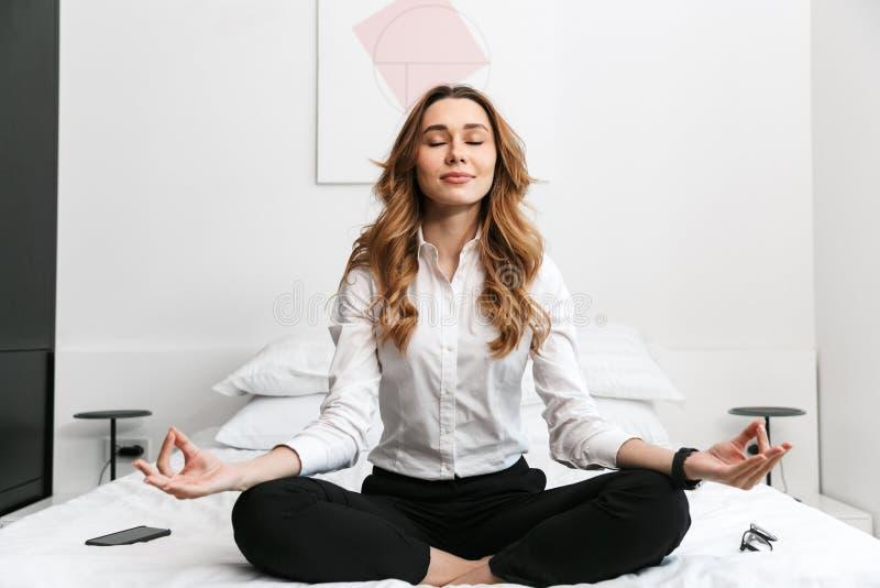 Η επιχειρησιακή γυναίκα έντυσε στο επίσημο πουκάμισο ενδυμάτων καθμένος στο εσωτερικό στο κρεβάτι meditate στοκ εικόνες