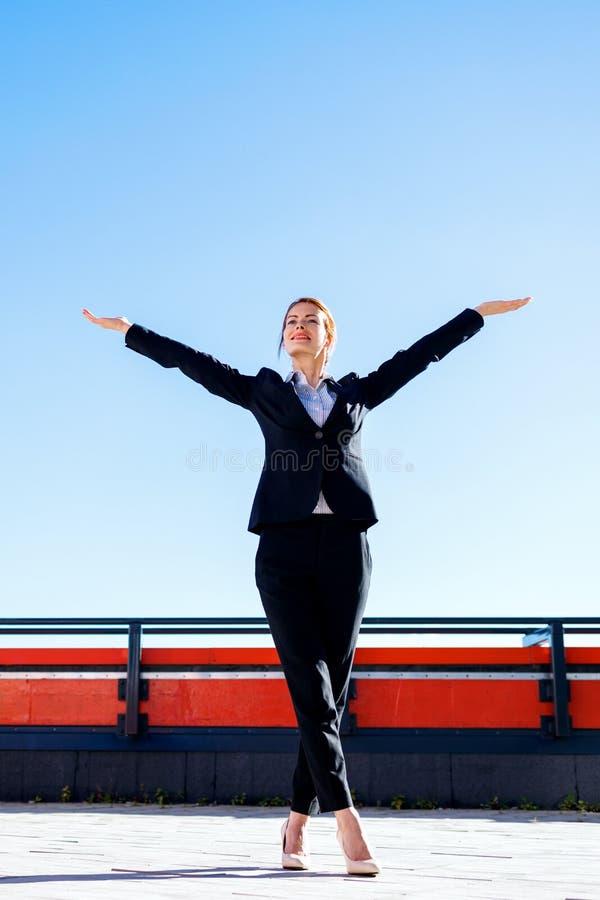 Η επιχειρησιακή γυναίκα αισθάνεται το θρίαμβο στη γέφυρα παρατήρησης στοκ φωτογραφίες