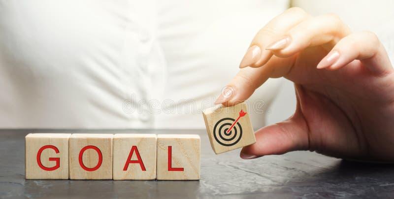 Η επιχειρησιακή γυναίκα κρατά τους ξύλινους φραγμούς με το στόχο λέξης Η έννοια της επίτευξης των επιχειρησιακών στόχων Επίτευξη  στοκ εικόνες