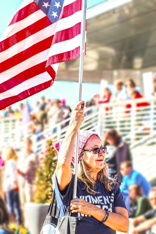 Η ηλικιωμένη γυναίκα με το πουκάμισο γραμμάτων Τ σημαιών και Μαρτίου των γυναικών στην πολιτική συνάθροιση με το πλήθος θόλωσε πί στοκ εικόνες με δικαίωμα ελεύθερης χρήσης