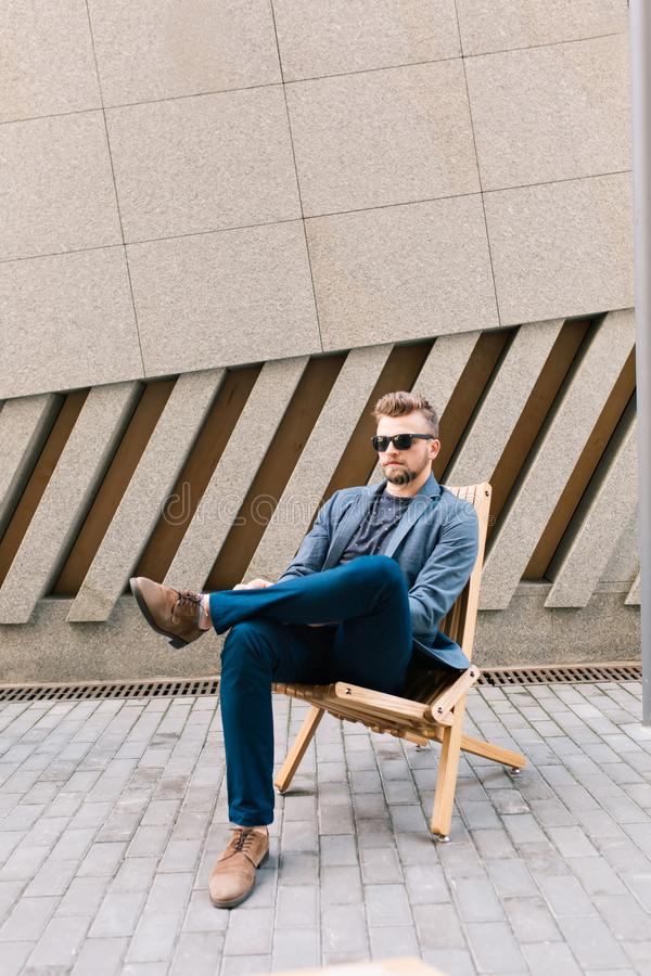Η κάθετη φωτογραφία του όμορφου τύπου κάθεται στην καρέκλα υπαίθρια στο υπόβαθρο συμπαγών τοίχων Φορά το γκρίζο σακάκι, τζιν στοκ φωτογραφίες