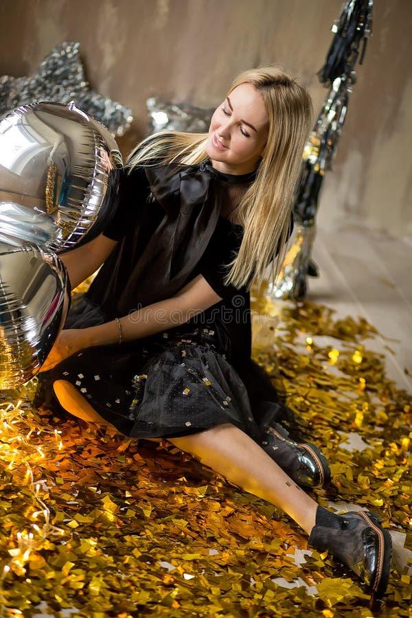 Η κατάπληξη της χαριτωμένης κυρίας που γιορτάζει τη νέα γιορτή γενεθλίων έτους, που θέτει στο χρυσό λάμπει υπόβαθρο και ρίψη του  στοκ φωτογραφία