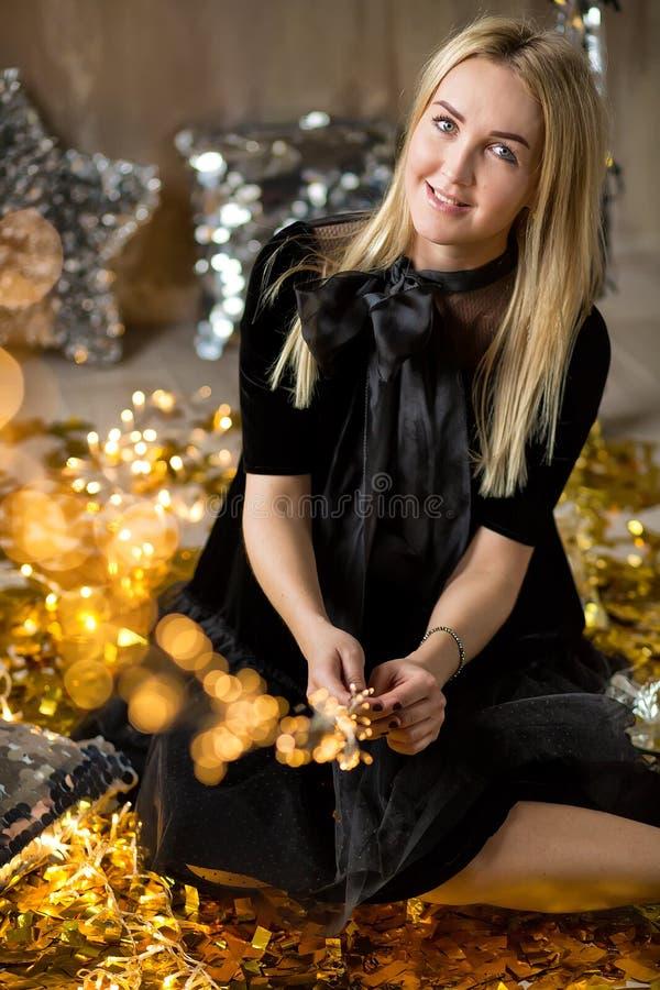 Η κατάπληξη της χαριτωμένης κυρίας που γιορτάζει τη νέα γιορτή γενεθλίων έτους, που θέτει στο χρυσό λάμπει υπόβαθρο και ρίψη του  στοκ εικόνες με δικαίωμα ελεύθερης χρήσης