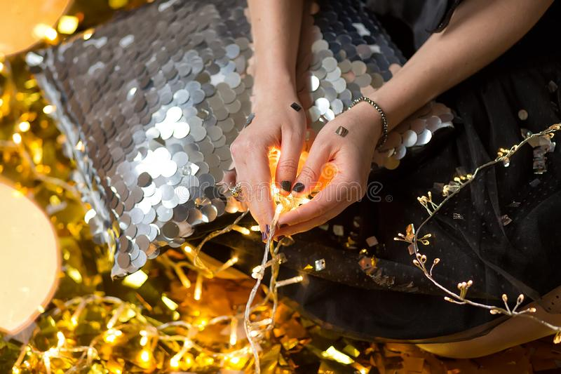 Η κατάπληξη της χαριτωμένης κυρίας που γιορτάζει τη νέα γιορτή γενεθλίων έτους, που θέτει στο χρυσό λάμπει υπόβαθρο και ρίψη του  στοκ φωτογραφίες