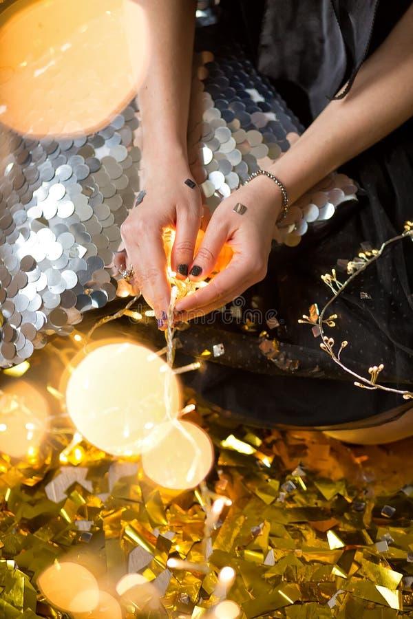 Η κατάπληξη της χαριτωμένης κυρίας που γιορτάζει τη νέα γιορτή γενεθλίων έτους, που θέτει στο χρυσό λάμπει υπόβαθρο και ρίψη του  στοκ φωτογραφίες με δικαίωμα ελεύθερης χρήσης